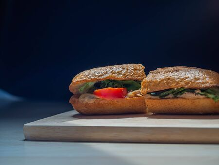 Bad serving food of poor quality tuna sandwich with not fresh vegetable on wooden plate and gradient black background.
