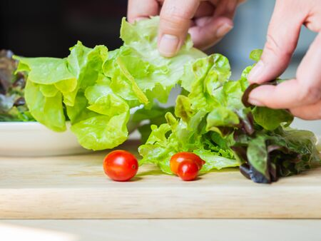 Green salad vegetables and red small tomatoes cooking on wooden plate in the kitchen. Imagens