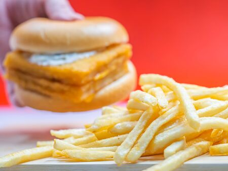 Closeup of french fried with blurry fish burger, woman 's hand and red background.
