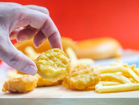 Closeup of crispy nuggets and woman 's hand with blurry french fried, fish burger and red background.
