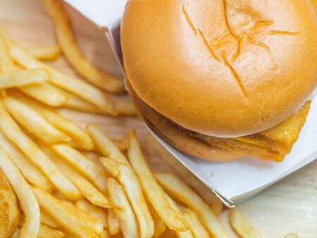 Top view or directly above of closeup fish burger in paper box and frenchfried on wooden table. Imagens - 141199230