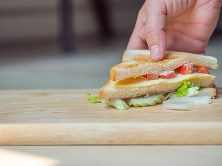 Cooking sandwich with woman 's hand and wooden cutting board in the kitchen.