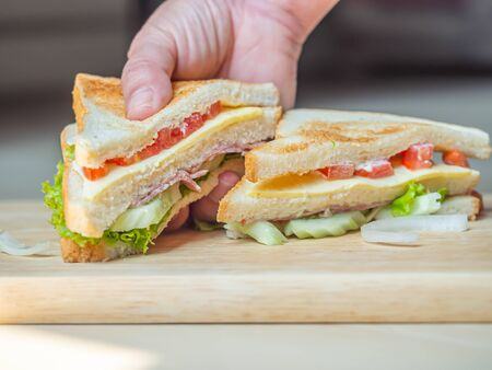 Cooking sandwich with woman 's hand and wooden cutting board in the kitchen. Imagens - 141229699