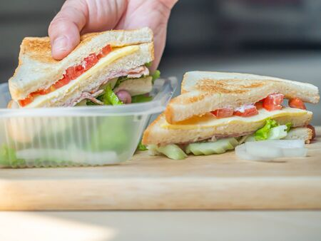 Cooking sandwich with woman 's hand and wooden cutting board in the kitchen. Cooking concepts or plastic environment impact or problem ideas. Imagens - 141229754