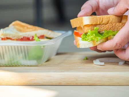 Cooking sandwich with woman 's hand and wooden cutting board in the kitchen. Cooking concepts or plastic environment impact or problem ideas. Imagens