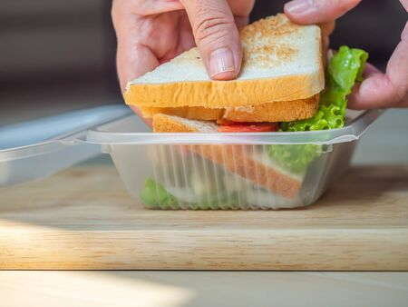 Cooking sandwich with woman 's hand and wooden cutting board in the kitchen. Cooking concepts or plastic environment impact or problem ideas. Imagens - 141229708