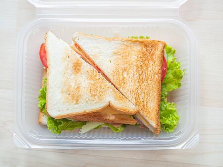 Top view or directly above of sandwich in plastic box, cooking for breakfast, lunch, dinner or picnic time on wooden table and cutting board in the kitchen.