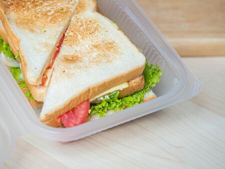 Sandwich in plastic box, cooking for breakfast, lunch, dinner or picnic time on wooden table and cutting board in the kitchen. Imagens - 141241005
