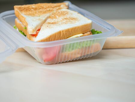 Sandwich in plastic box, cooking for breakfast, lunch, dinner or picnic time on wooden table and cutting board in the kitchen.