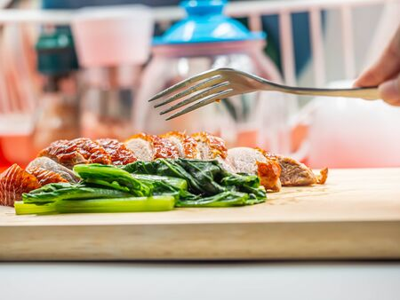 Closeup of sliced roasted duck, green vegatable, fork on wooden cutting board and woman 's hand with blurry kitchen background. Imagens - 141975602