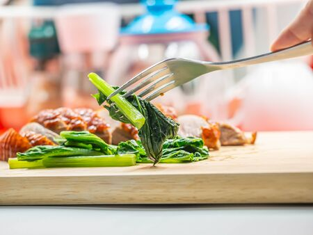 Closeup of sliced roasted duck, green vegatable, fork on wooden cutting board and woman 's hand with blurry kitchen background. Imagens