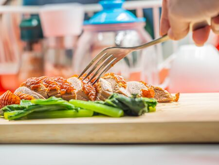 Closeup of sliced roasted duck, green vegatable, fork on wooden cutting board and woman 's hand with blurry kitchen background. Imagens - 141975662