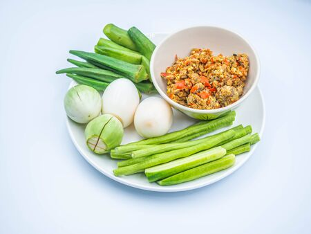 Thai chili sauce (Nam Prik) in the ceramic bowl with boiled eggs and vegatables on ceramic dish and gray background.