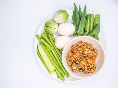 Top view or directly above of Thai chili sauce (Nam Prik) in the ceramic bowl with boiled eggs and vegatables in ceramic dish and gray background. Imagens - 142144572