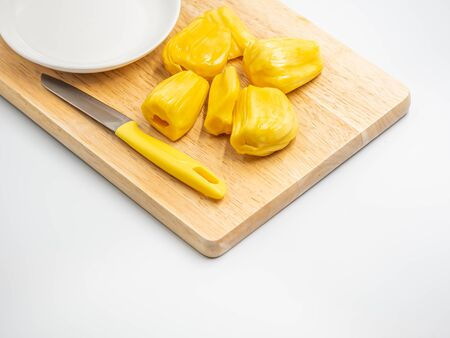 Closeup of yellow ripe jackfruit, knife, white ceramic dish on wooden cutting board in the kitchen or restaurant. Imagens