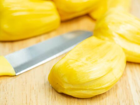 Closeup of yellow ripe jackfruit and knife on wooden cutting board in the kitchen or restaurant. Imagens