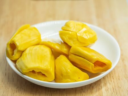 Closeup of yellow ripe jackfruit on white ceramic dish and wooden table in the kitchen or restaurant.