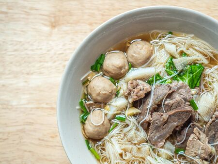 Top view or directly above of Thai braised beef noodle soup in ceramic bowl on blurry wooden table background in the kitchen or restaurant.