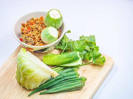 Thai chili sauce (Nam Prik) in the ceramic bowl with vegatables on wooden cutting board and gray background. Imagens