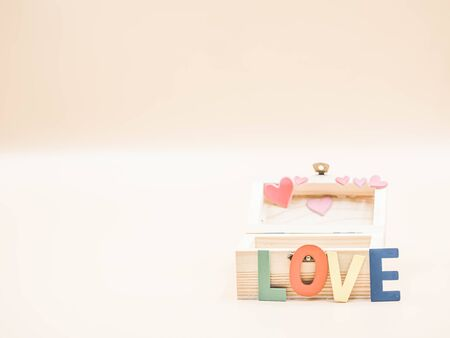 Selective focus at wooden multicolored alphabet word love and box with blurry pink pastel color heart sticker and background. Imagens