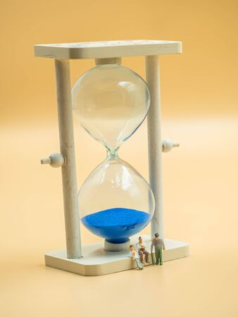 Sand glass and miniature figure of adolescence, adult and elder with blurry golden color background for life stages and time concept and idea. Imagens - 143434065