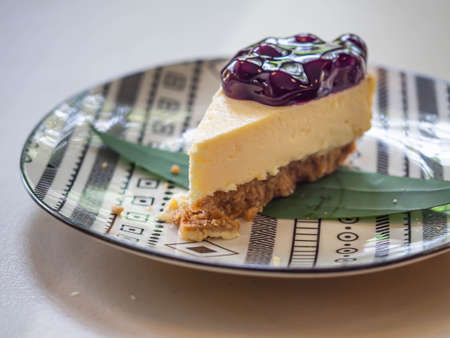 Closeup of blueberry cheese cake pie on ceramic plate on grey table in restaurant or cafe for dessert time concept.