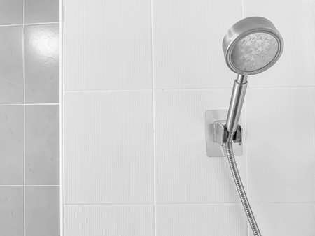 Closuep of stainless steel head shower with blurry white and gray tile wall in the bathroom. Imagens