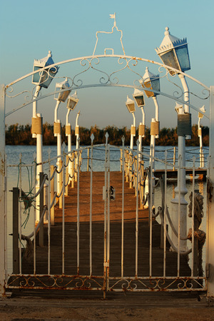 A pier to the sea with a gate and lights at sunset Stock Photo