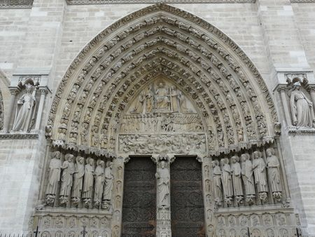Arched doorway and wooden doors at Notre Dame Cathedral in Paris, France