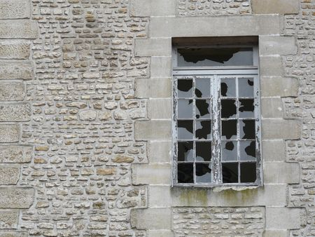 sabotage: Broken windows in a derelict stone building