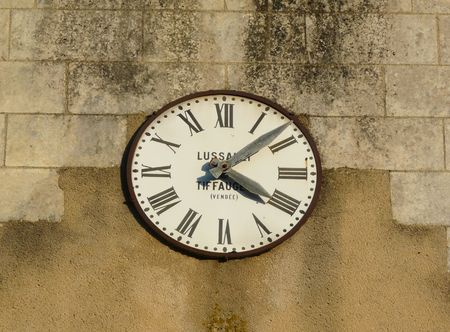 Old clock with Roman numerals on the exterior of a church Stock Photo