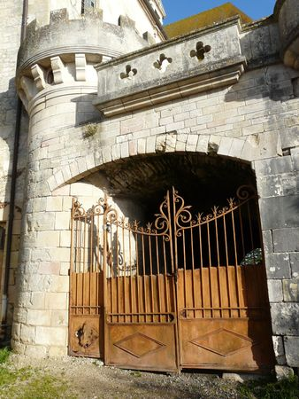 Old arched gateway with rusty iron gate at the Abbey in Saint Savin, France