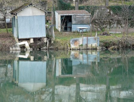 edge: Old garden and fishing sheds on the rivers edge Stock Photo