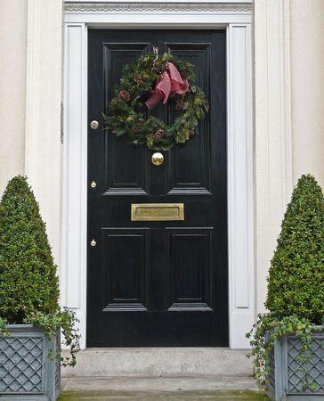 Shiny black door with Christmas wreath