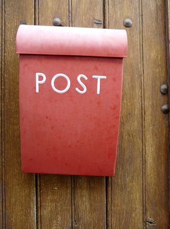 Red mailbox or letterbox on a wooden door