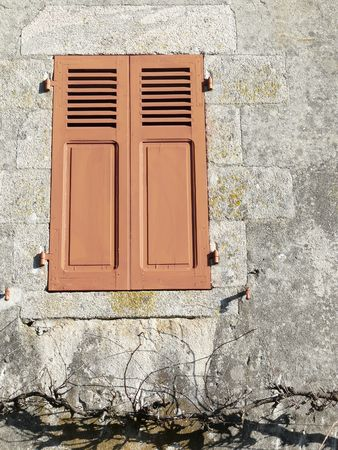 Closed brown shutters on a window of a house in France Stock Photo