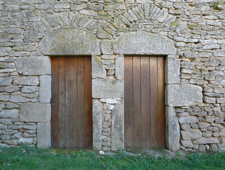 Small wooden doors in a stone building in the countryside Stock Photo