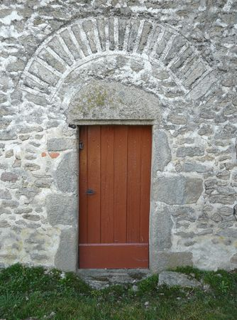 Small wooden door in a stone building in the countryside photo