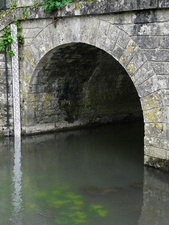 Old stone arched bridge in the countryside in France with river level measure