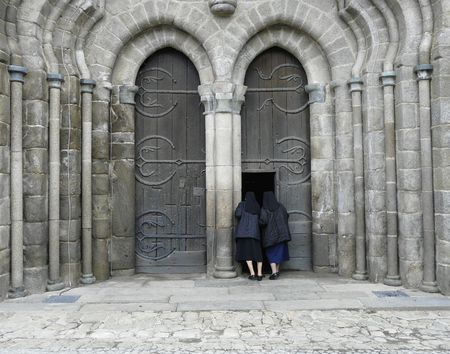 Two nuns peering in through a huge wooden door of a medieval church in Le Dorat, France Stock Photo