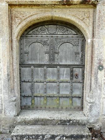 Old wooden arched door at Lanhydrock Castle near Bodmin in Cornwall England