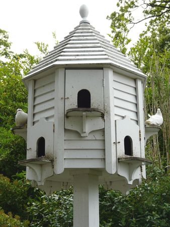 White wooden dovecot for pigeons with small arched doorways