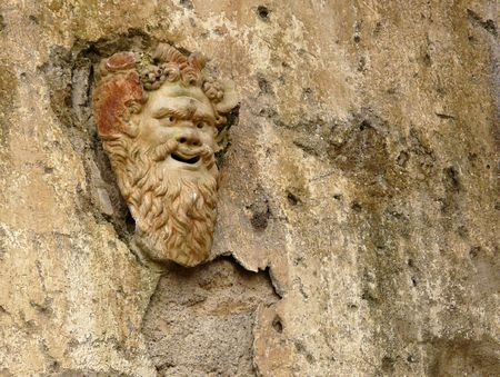 Ancient stone mask on a wall at the ancient Roman city of Herculaneum, which was destroyed and buried during the eruption of Mount Vesuvius in 79 AD Stock Photo