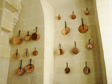 Shiny copper pots and pans hanging on the wall of a medieval castle's kitchen