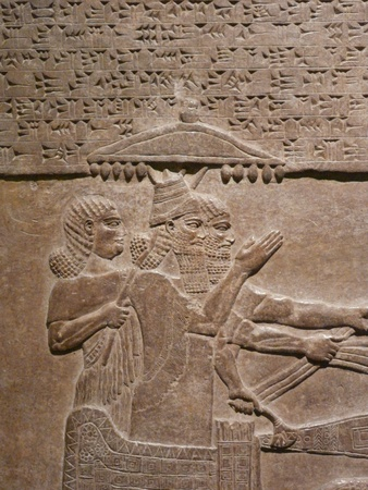 relics: Ancient Assyrian wall carvings of men and cuneiform writing Stock Photo