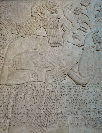 Ancient Assyrian wall carvings of men and cuneiform writing Stock Photo