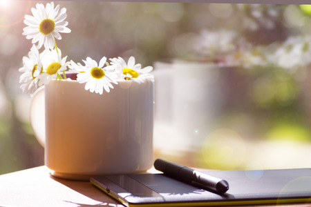 Mug, daisies, graphics tablet. The concept of am designer. A Sunny summer morning. Stock Photo