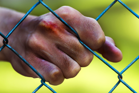 incarcerated: Man hands in jail. Imprisonment. Poverty, suffering.
