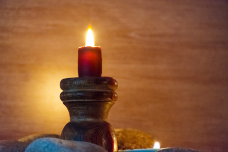 candlelit: Several multi-colored candles are lit and surrounded by stones.