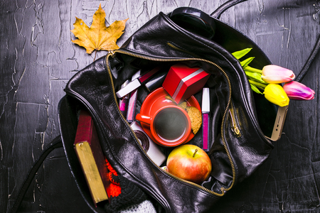 The contents of the female handbag. Flowers, lipstick, camera, coffee, biscuits, beads. Dark background. Stock Photo